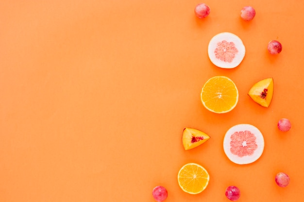 Fruit slices of orange; grapefruit and peach with grapes on an orange backdrop Free Photo