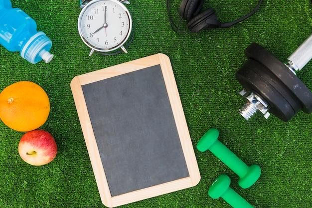 Fruit; water bottle; alarm clock; headphone; dumbbells on wooden blank slate on green turf Free Photo
