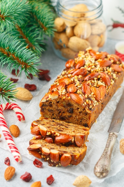 Fruitcake. traditional christmas cake with almonds, dried cranberries, cinnamon, cardamom, anise, cloves Premium Photo