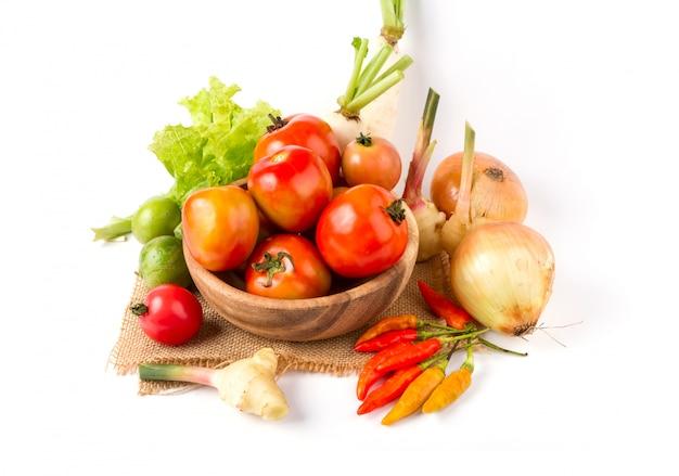 果物と野菜の白い背景の上の木製のボウル Premium写真