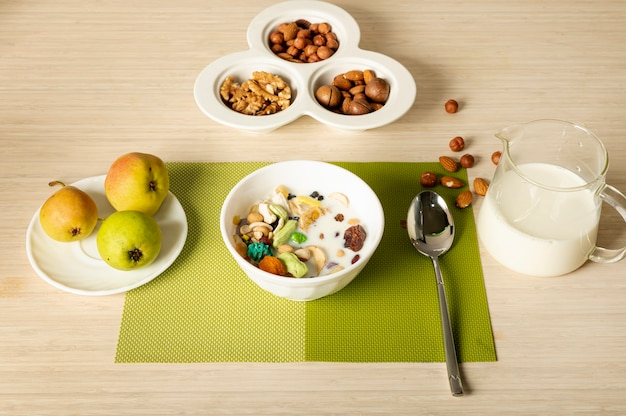 Fruits, nuts  and cereal breakfast arrangement on plain background Free Photo