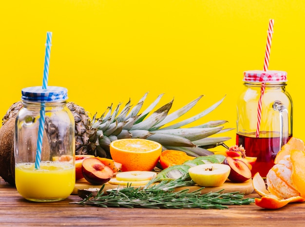 Fruits; rosemary and juice mason jar on chopping board against yellow backdrop Free Photo