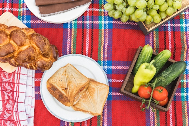 Fruits; sandwiches and baked braided bread loaf on checkered tablecloth Free Photo