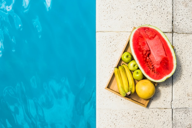 Fruits on tray placed on border of pool Free Photo