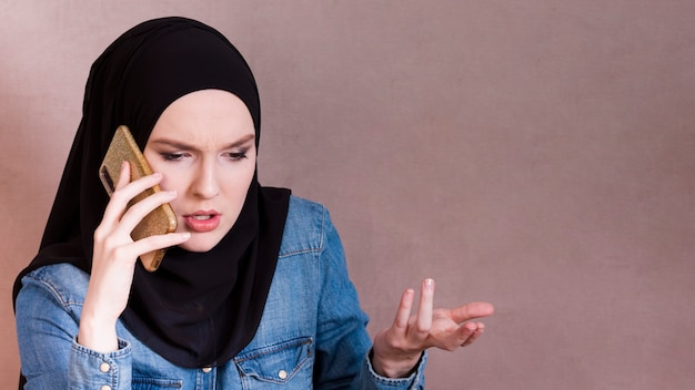 Frustrated; arab woman talking on smartphone making hand gesture Free Photo