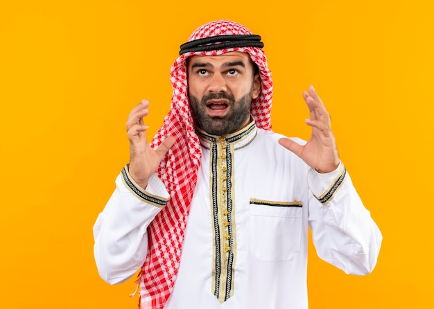 Free Photo | Frustrated arabic businessman in traditional wear shouting with raised hands standing over orange wall