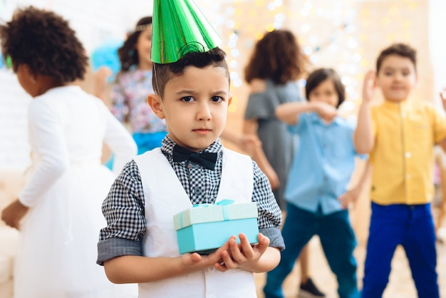 Frustrated boy in green hat is standing in room at birthday. Premium Photo