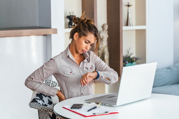 Frustrated business woman at work looking at wristwatch. Premium Photo