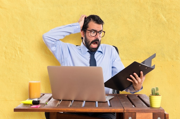 Frustrated businessman in his office with his folder Free Photo