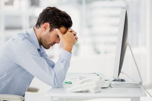 Frustrated businessman sitting on desk with hand on head Premium Photo