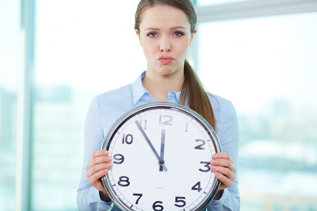Frustrated businesswoman holding a big clock Free Photo