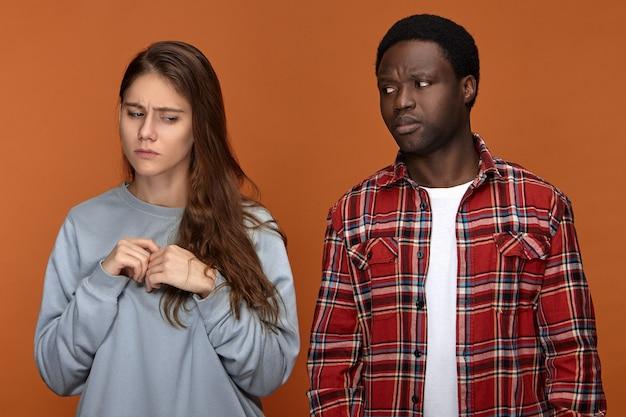 Una ragazza europea di 20 anni frustrata si sente nervosa a causa del disaccordo con il suo ragazzo afroamericano deluso e scontento. concetto di persone, etnia, relazioni, litigi e problemi Foto Gratuite