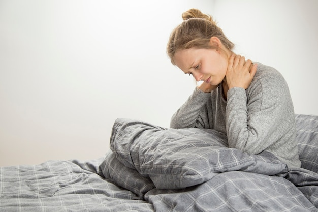 Frustrated girl feeling neck ache Free Photo