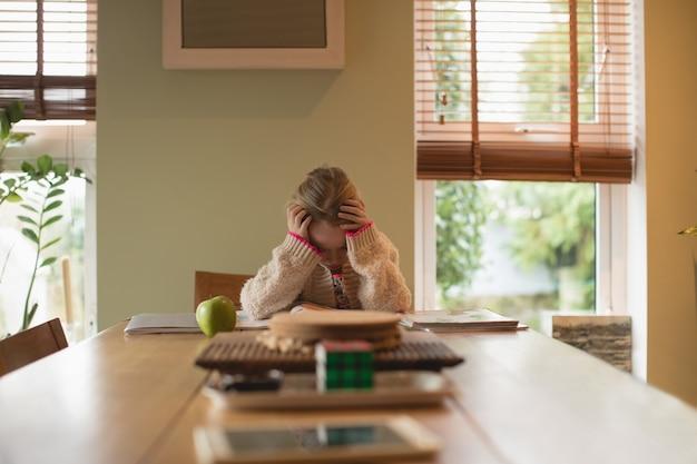 Разочарованная девушка сидит за столом и учится в гостиной Бесплатные Фотографии