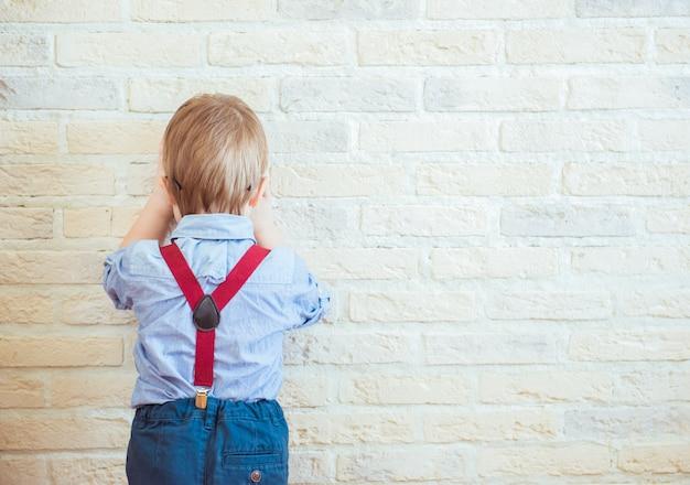 Разочарованный маленький мальчик, стоящий возле стены отвернулся Premium Фотографии