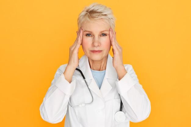 頭痛や片頭痛に悩まされ、こめかみに触れて痛みを和らげ、疲れたストレスのある表情をしている定年の欲求不満の成熟した女性女性医師。ストレスと否定的な感情 無料写真