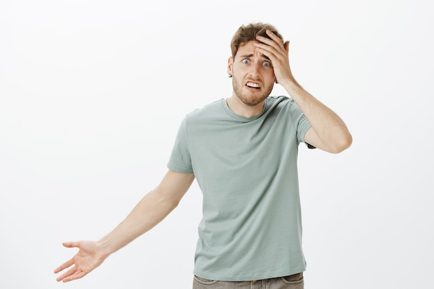 Frustrated nervous young male model in t-shirt, touching palm and spreading hand in clueless gesture, feeling worried and confused, having no idea how help and what do Free Photo