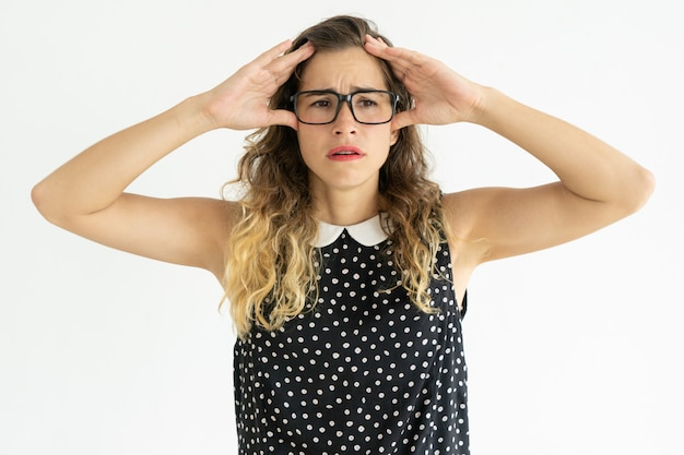 Frustrated pretty young woman touching head Free Photo