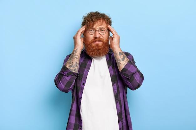 두꺼운 수염을 가진 좌절 된 빨간 머리 남자가 관자놀이에 닿고 거대한 편두통으로 고통 받고 진통제가 필요합니다. 무료 사진
