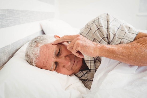 Frustrated senior man lying on bed in bedroom Premium Photo