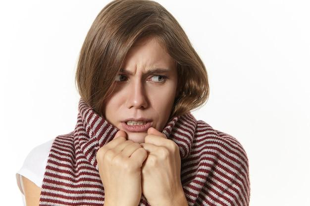 Giovane femmina malata frustrata avvolta in una sciarpa a strisce che si congela a causa dell'alta temperatura, soffre di raffreddore o influenza, accigliata, con espressione facciale dolorosa, posa isolata Foto Gratuite