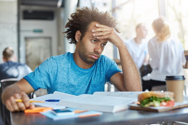 Frustrated stressed out male student sitting at cafe table with books, notes and lunch, having tired exhausted look while failing to solve mathematical problem. Free Photo