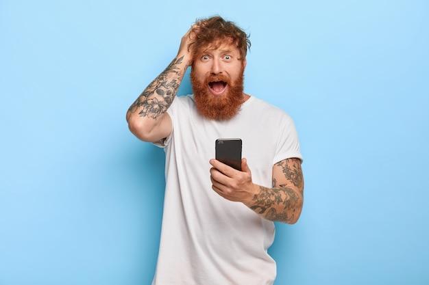 欲求不満のストレスの多い生姜ヒップスターは、頭を抱え、心配そうな表情で見え、口を開け、現代の携帯電話を保持し、間違いのために恐怖を感じ、アプリで何か間違ったことをしました 無料写真