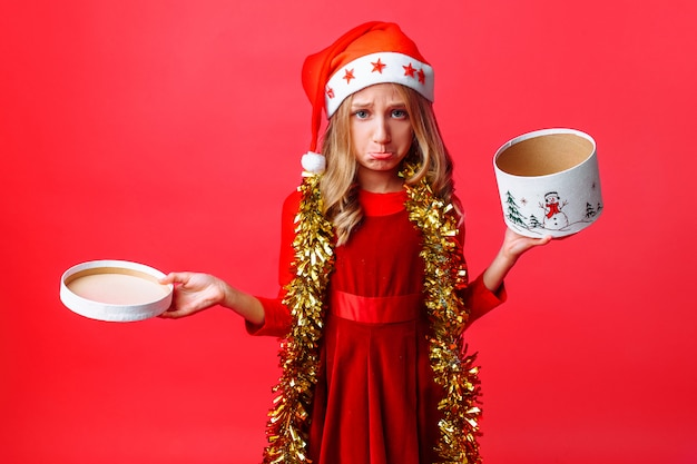 산타 모자와 목 오프닝 상자에 반짝이 좌절 된 십 대 소녀, 프리미엄 사진