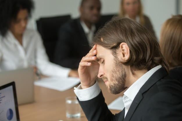 Frustrated tired businessman having strong headache at diverse team meeting Free Photo