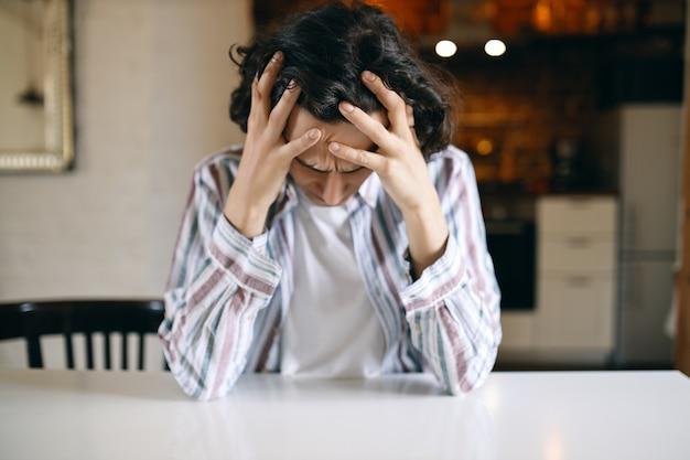 우울한 표정을 짓고, 내려다보고, 머리에 손을 얹은 좌절 한 불행한 청년은 그가 해고되어 재정적 문제로 스트레스를 받았습니다. 무료 사진