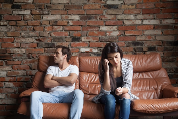 Frustrated upset couple after quarrel sitting on sofa at home Free Photo