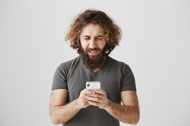 Uomo del medio oriente frustrato e sconvolto che guarda il telefono in difficoltà Foto Gratuite