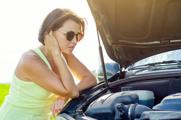 Frustrated woman driver near broken car. Premium Photo