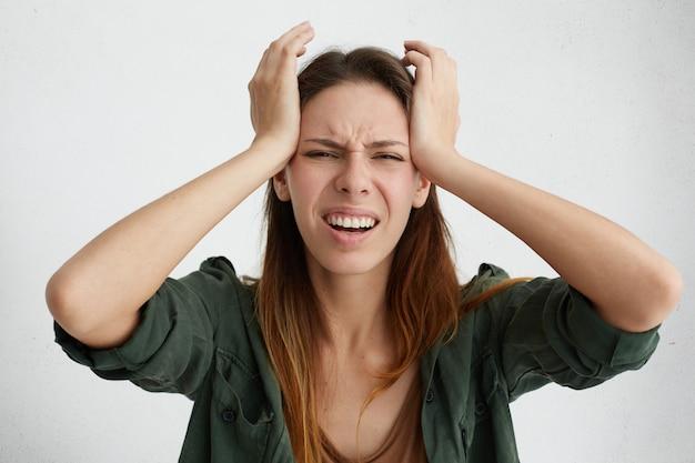 Donna frustrata che ha un terribile mal di testa tenendo le mani sulla testa aggrottando le sopracciglia con dolore che sembra infelice e stressante. casalinga in preda alla disperazione avendo situazione stressante nella sua sofferenza di vita Foto Gratuite