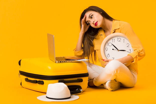 Frustrated woman holding clock and looking at laptop on top of luggage Free Photo