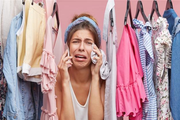 Разочарованная женщина стоит возле стойки, полной одежды, болтает с подругой по смартфону, жалуется, что ей нечего надеть, с ужасным выражением лица. одежда, концепция моды Бесплатные Фотографии
