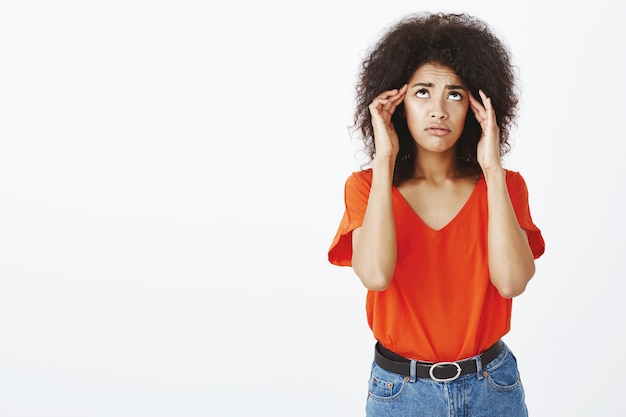 Frustrated woman with afro hairstyle posing in the studio Free Photo