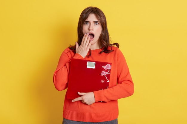 Frustrated woman with scale in hands posing over yellow, female being very shocked Free Photo