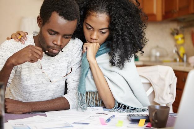 Giovane coppia africana frustrata che ha grossi problemi a pagare le bollette Foto Gratuite