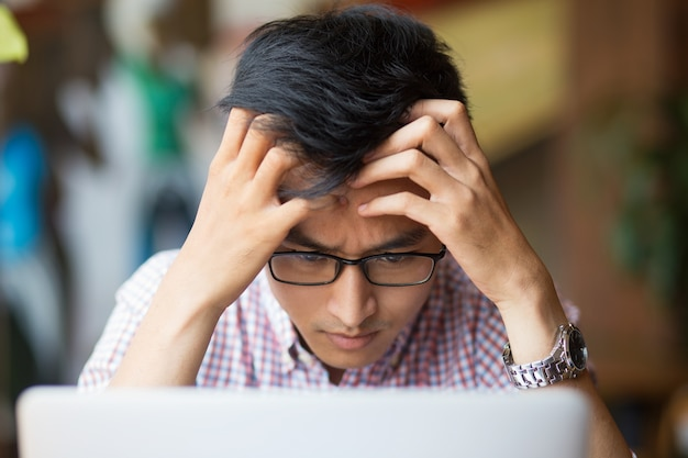 Frustrated young asian man sitting at laptop Free Photo