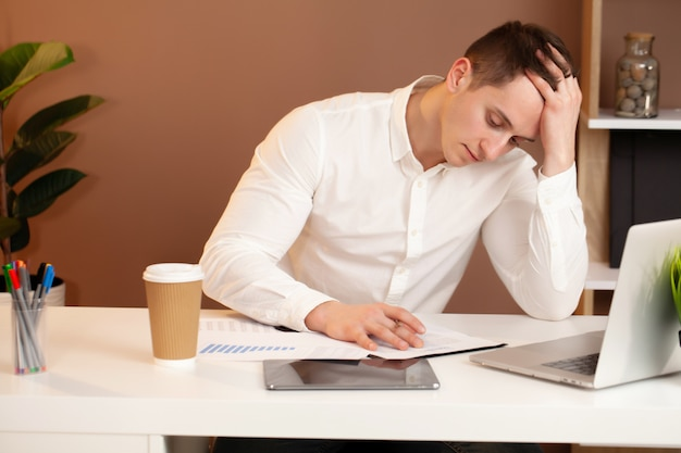 Frustrated young business man working on laptop at office Premium Photo