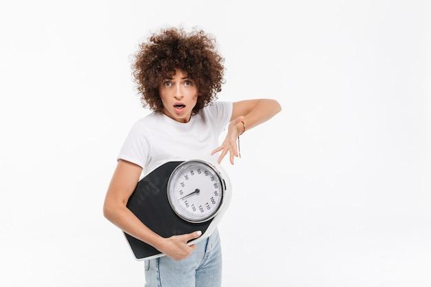 Giovane donna casuale frustrata che indica ai pesi Foto Gratuite