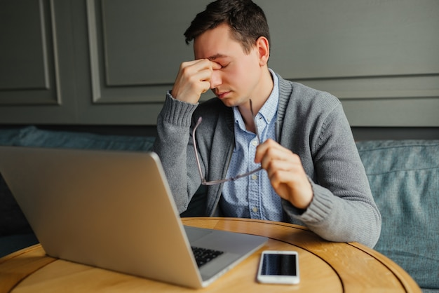 Frustrated young man massaging his nose and keeping eyes closed while working Free Photo