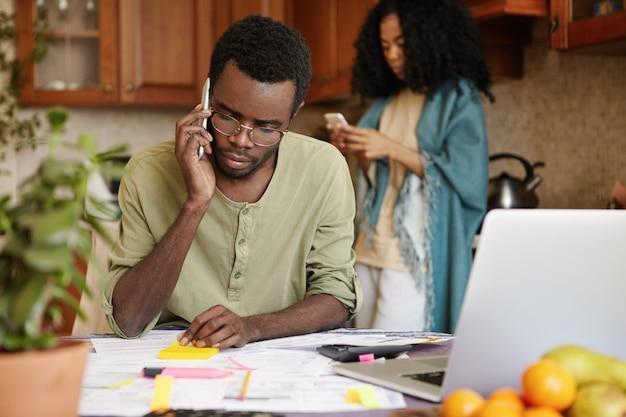 Разочарованный молодой безработный африканец разговаривает по мобильному телефону со своим другом, просит у него денег для покрытия семейных расходов, но не может больше оплачивать счета за коммунальные услуги, потому что его уволили Бесплатные Фотографии