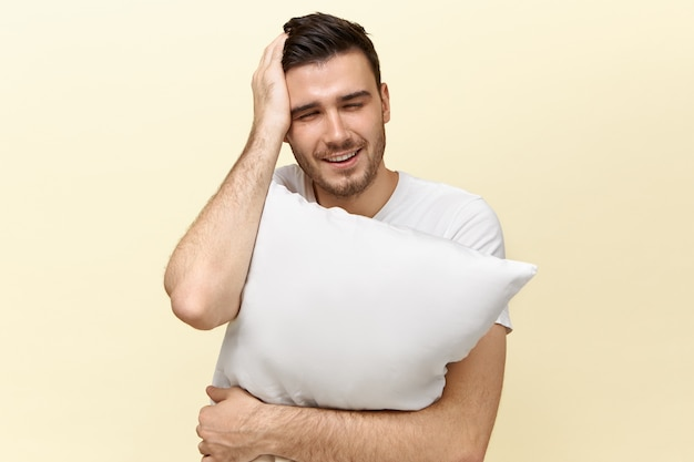 Frustrated young unshaven male embracing white pillow and holding hand on his head having hangover, suffering from headache because of sleepless night, having sleepy tired facial expression Free Photo