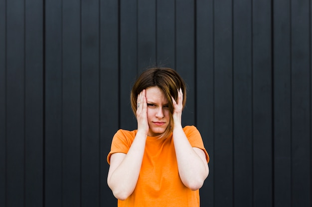 Frustrated young woman against black striped backdrop Free Photo
