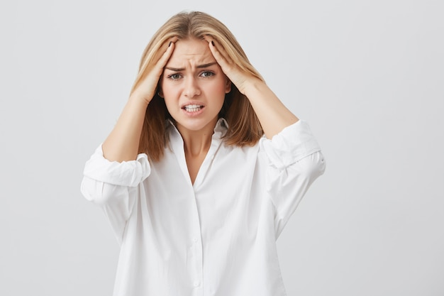 Frustrated young woman having terrible headache keeping hands on head frowning her face with pain looking unhappy and stressful. female student in despair having stressful situation at university. Free Photo