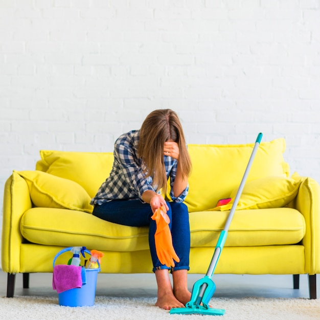 Frustrated young woman sitting on sofa with cleaning equipments Free Photo
