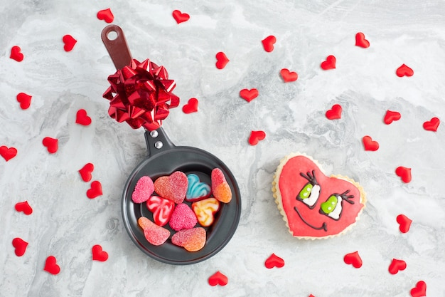 Frying pan with candies heart-shaped and cookies on festive Premium Photo