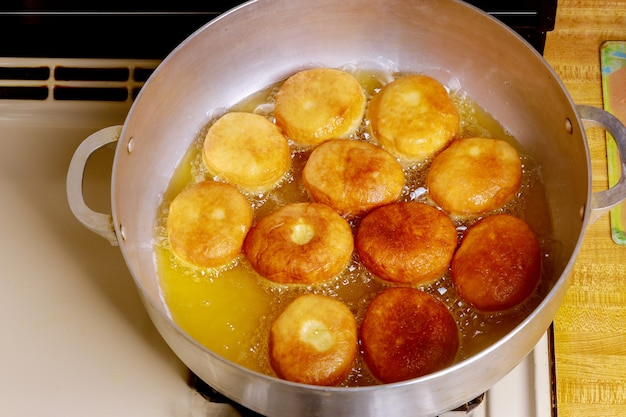 Frying round tasty donuts in hot oil in deep pan. Premium Photo